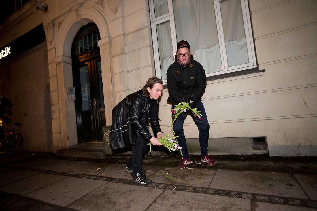 Två unga män med huvor och svarta sjalar för ansiktet går fram och lägger ett gäng tulpaner. Sen försvinner de snabbt från platsen. Malthe och Sebastian plockar upp blommorna och slänger dem.