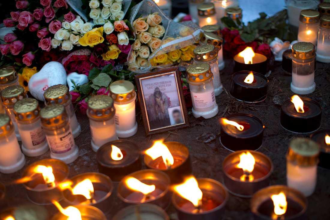 En stor mängd blommor och ljus på platsen i Uddevalla där tre personer hittades skjutna till döds.