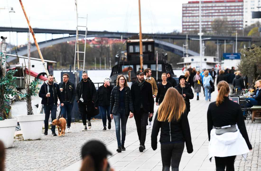 Personer flanerar på Norr Mälarstrand i Stockholm under en söndag i slutet av april.