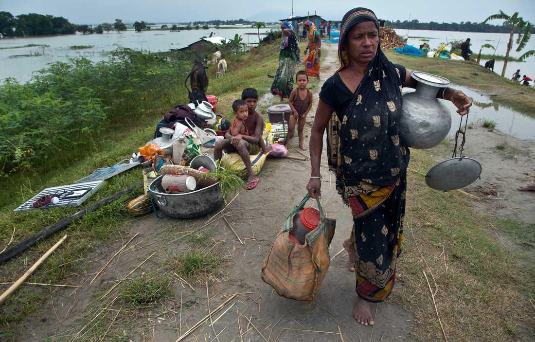 En indisk kvinna bär på sina saker när hon söker skydd från regnen i staden Guwahati i delstaten Assam.