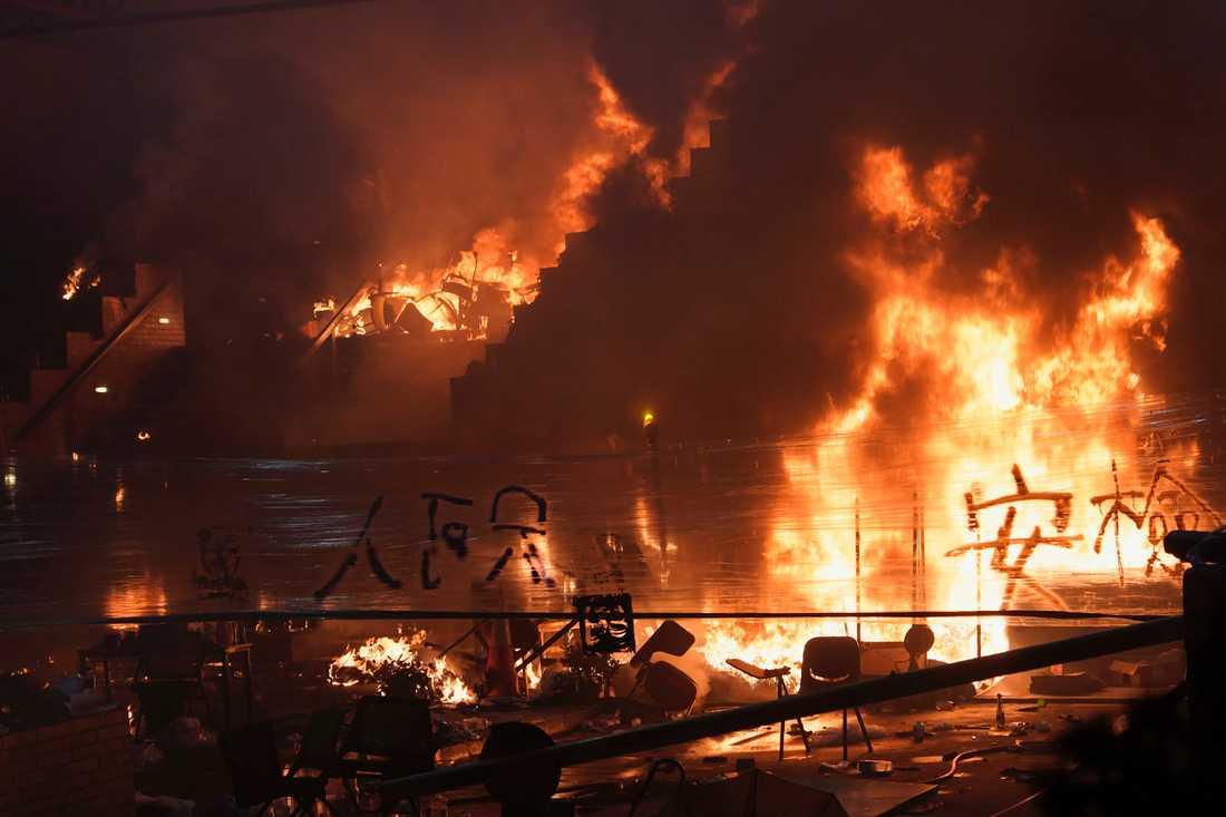 Demonstranter sätter eld på bråte i en trappa som leder till polytekniska universitetet i Hongkong.