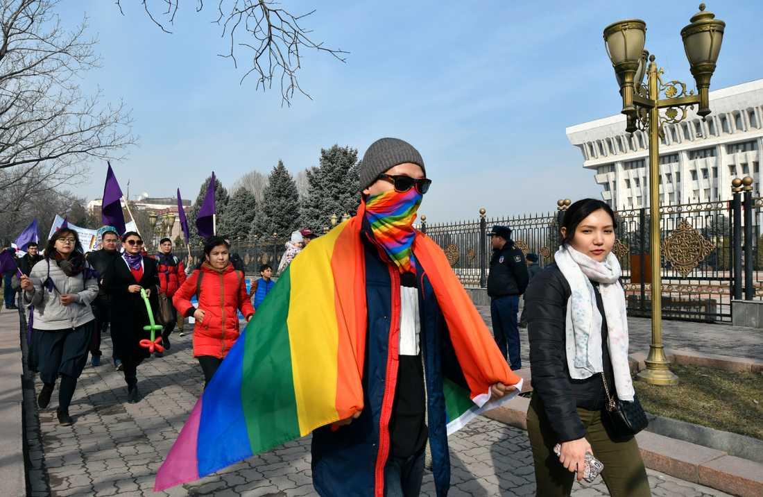 Människor marscherar förbi parlamentsbyggnaden i centrala Bisjkek i Kirgizistan på internationella kvinnodagen den 8 mars.