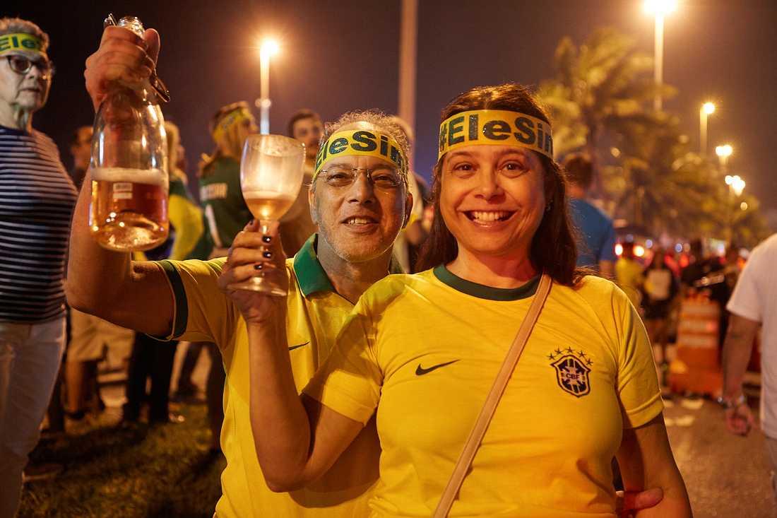 Celia Maria Barreto, 56  och hennes Marcos Rodrigues, 55, skålar i bubbel efter Bolsonaros vinst.