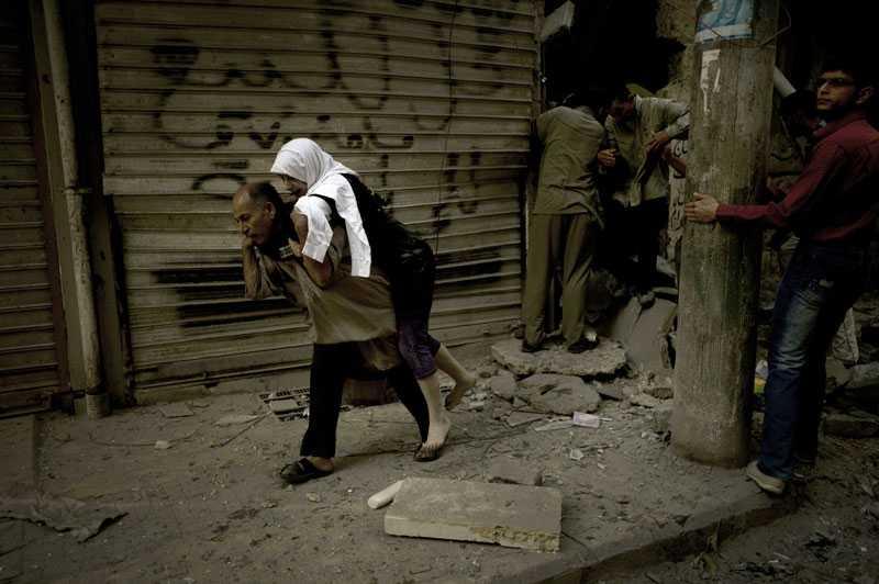 HENNES HEM ÄR I SPILLROR En skadad kvinna blir hjälpt i säkerhet efter att hennes hem förstörts i en attack i Aleppo.