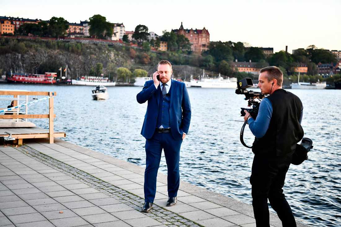 Mattias Karlsson (SD), stod en bit bort och talade i telefon under Åkessons tal på Riddarholmen.
