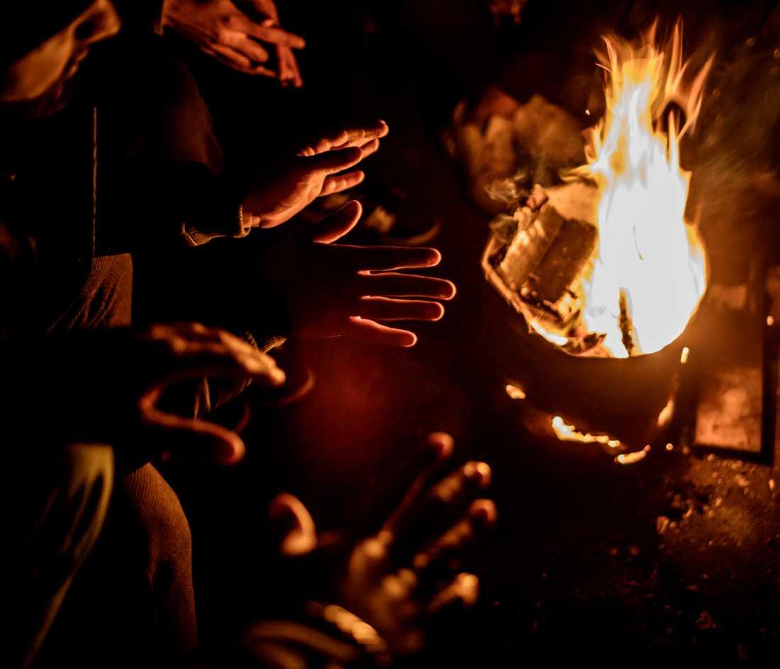 I den mörka lokalen finns ingen el och migranterna gör upp eld för att hålla värmen