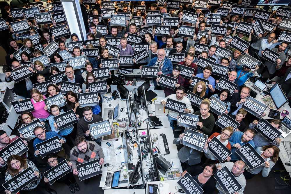 """Aftonbladets redaktion håller upp skyltar med texten """"Je Suis Charlie"""" – """"Jag är Charlie"""". Uttrycket har snabbt spridit sig över världen som ett sätt att visa sympati med offren."""