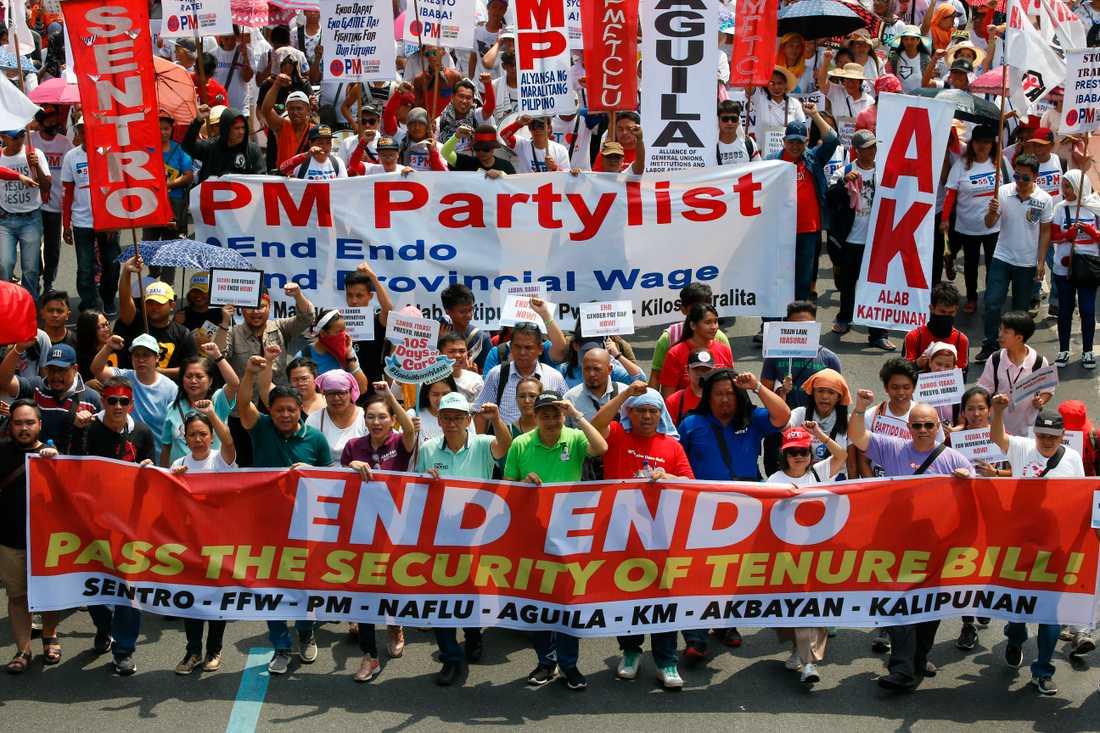 """Tusentals marscherar mot presidentpalatset i Manila, Filippinerna för att kräva att regeringen sätter stopp för en särskild typ av tillfälliga anställningsformer. På banderollen står ENDO – """"End of contract""""."""