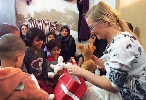 Hepaticas styrelseordförande Julia Kronlid delar ut julklappar till barn på ett flyktingcenter i Libanon. Vi vill ha samma möjlighet för våra projekt som övriga partier, skriver debattörerna.