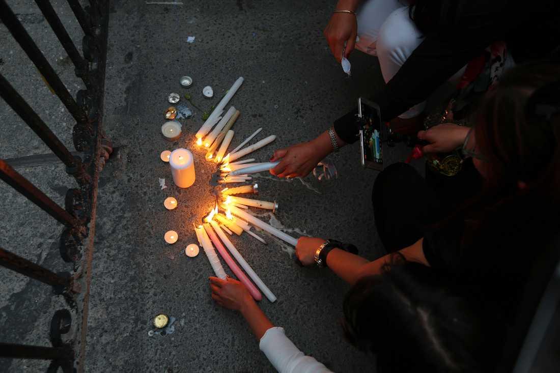 Kvinnor tänder ljus till minne av mördarens offer utanför presidentpalatset.