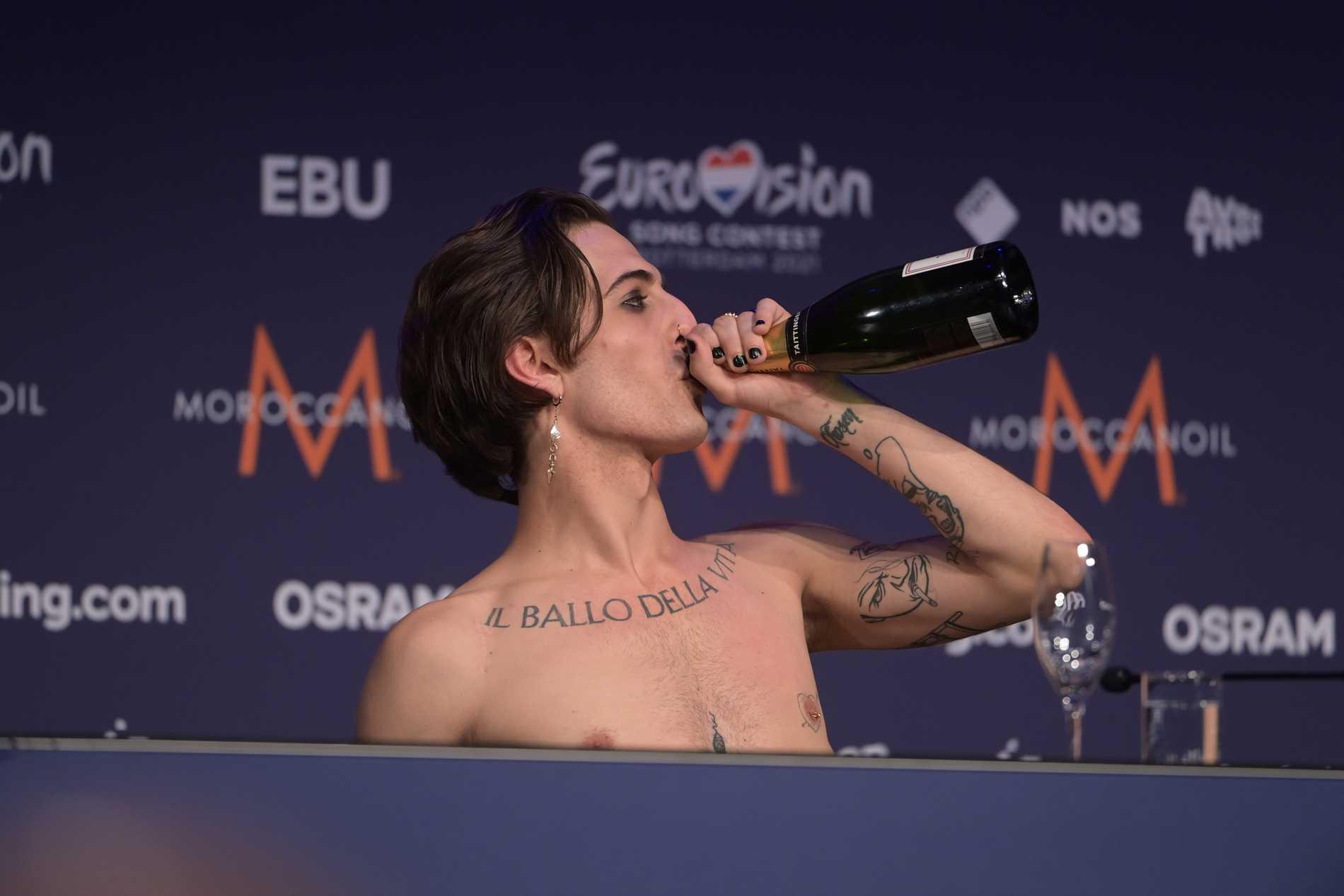 Måneskins Damiano David firar med att klunka champagne på presskonferensen.
