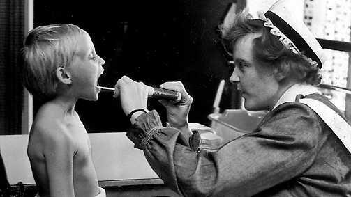 """Sjuksköterska i arbete 1960. Boken """"Göra gott"""" skildrar ett av världens äldsta yrken med medicinhistoriska referenser från Hippokrates till dagens stressade och utbrända sjukhuspersonal."""