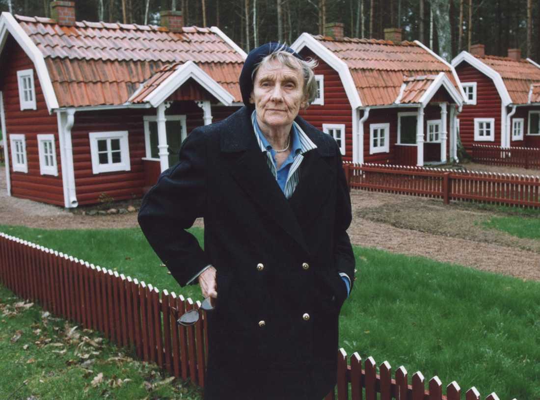 År 1999: Astrid Lindgren poserar framför röda stugor med vita knutar i Astrid Lindgrens Land i Vimmerby. Arkivbild.