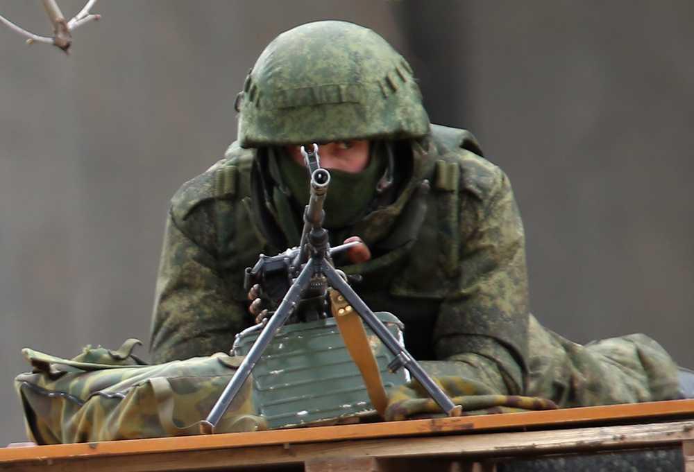 En oidentifierad beväpnad man håller vakt utanför en parlamentsbyggnad i Simferopol.
