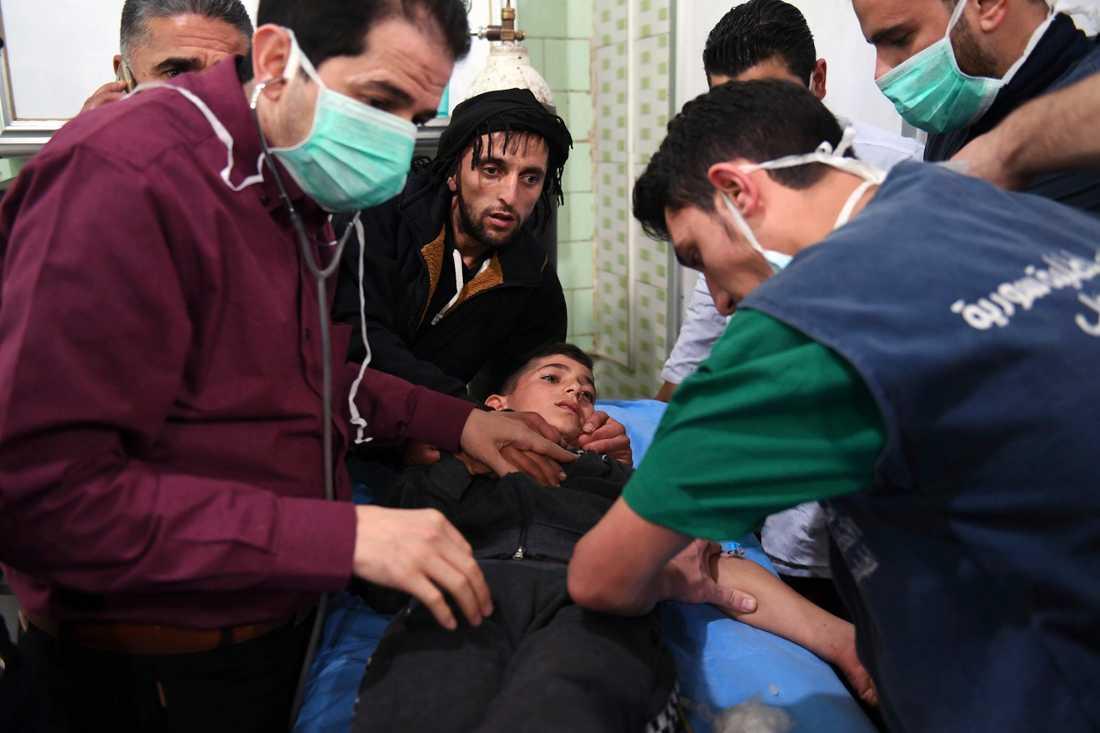 Sjukhuspersonal tar hand om en pojke som skadats i gasattacken i Aleppo.