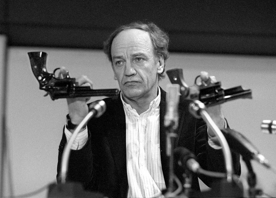 Länspolismästare Hans Holmér håller upp två revolvrar av märket Smith & Wesson 357 Magnum under en presskonferens på polishuset i Stockholm 31:a mars 1986. Detta slags vapen tros vara den typ av vapen som kan ha använts vid mordet på Sveriges statsminister Olof Palme.