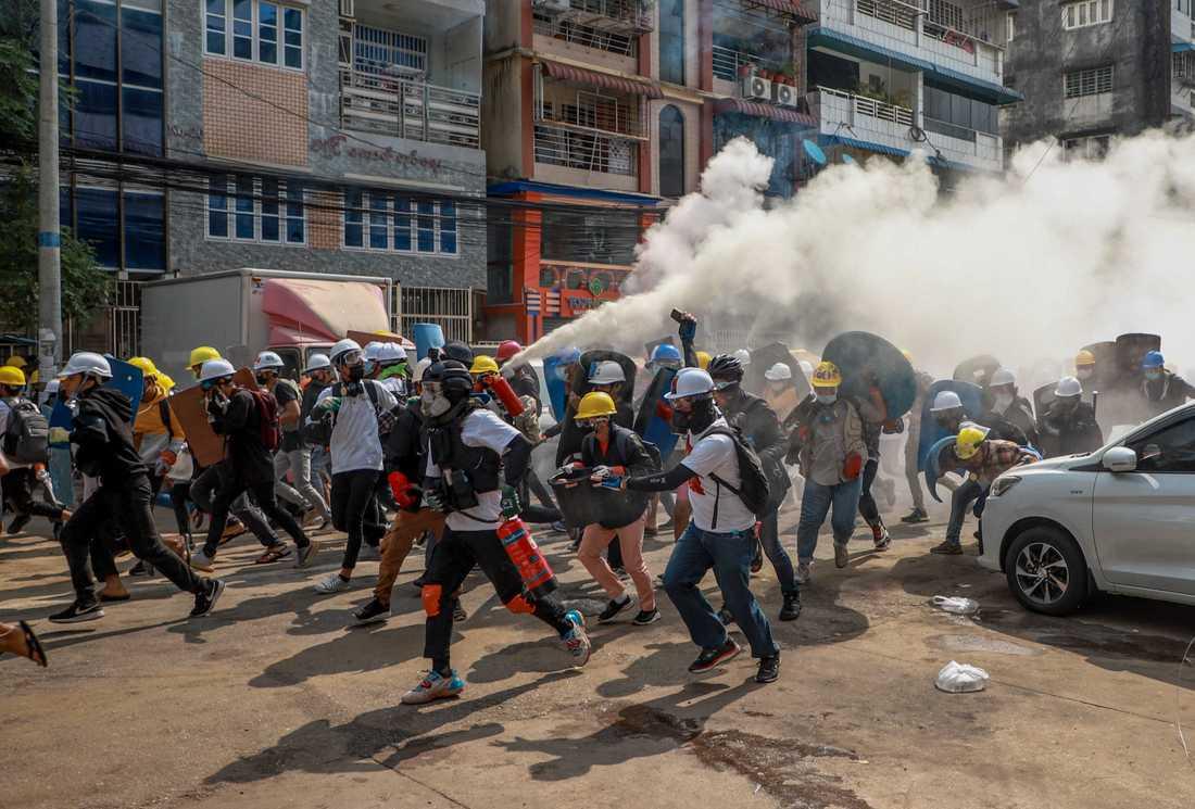 Onsdag 3 mars. Demonstranter använder brandsläckare för att motverka polisens tårgas i Rangoon. Man protesterar mot att militären tagit makten i landet.