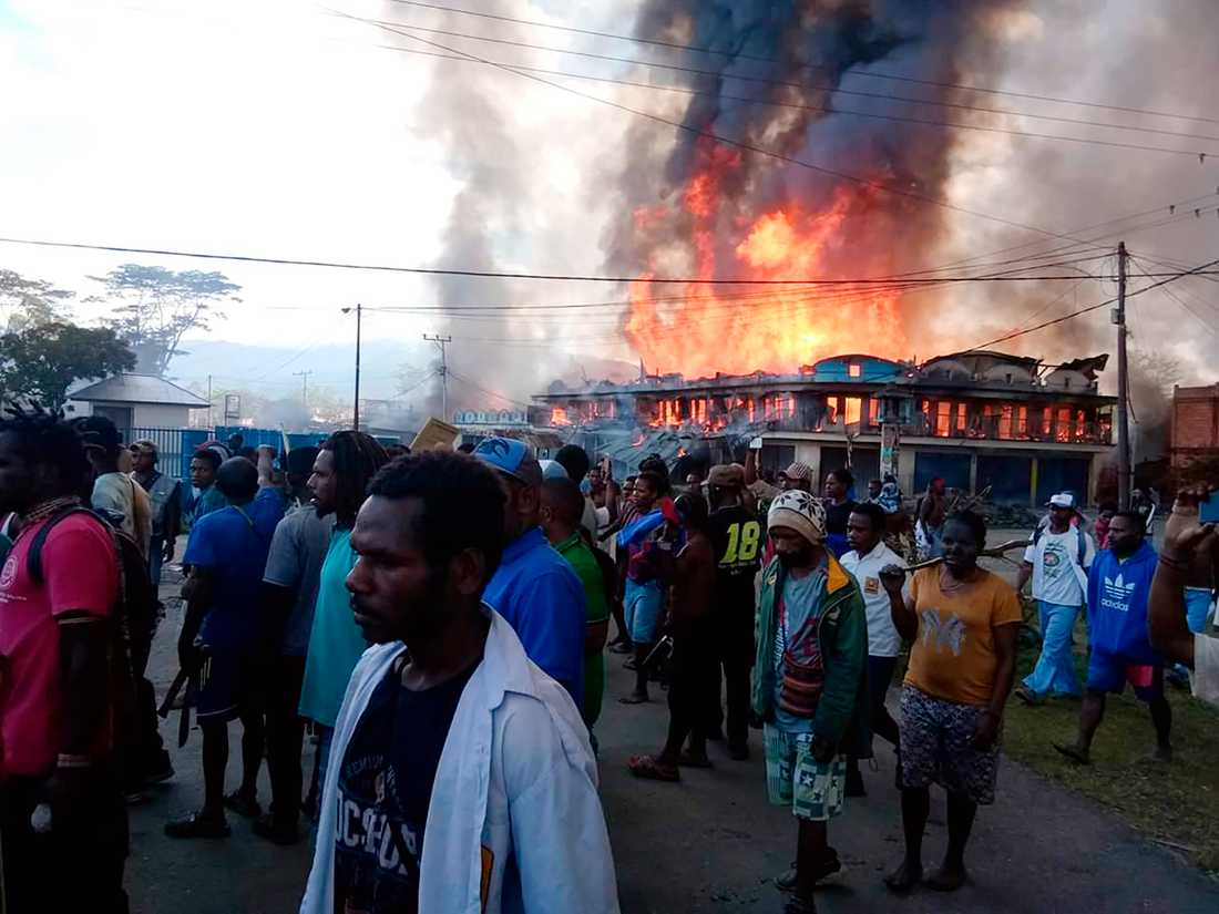 Folk samlas utanför butiker som satts i brand i Wamena i Papua.