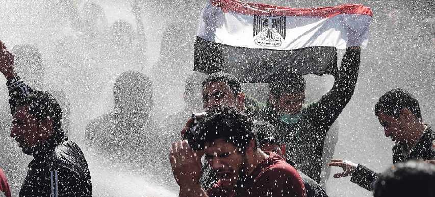 KAIRO I GÅR En demonstrant höjer den egyptiska flaggan samtidigt som polisen slår till med vattenkanoner.