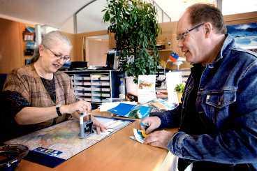 Aftonbladets reporter Sture Olsson passar på att få en stämpel i passet för 15 kronor av Marlise Huber-Schmitz på turistkontoret i Liechtenstein.