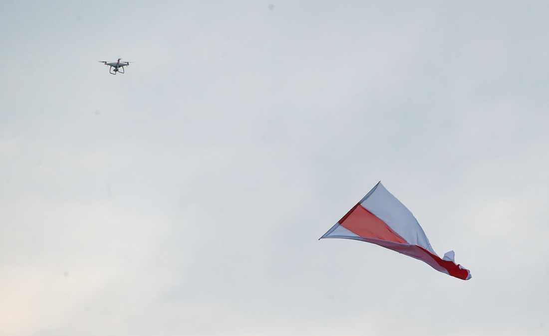 En drönare syns på himlen i Belarus huvudstad Minsk under en regimkritisk demonstration den 23 augusti. Landets gamla vit-röda flagga används som symbol av oppositionen.
