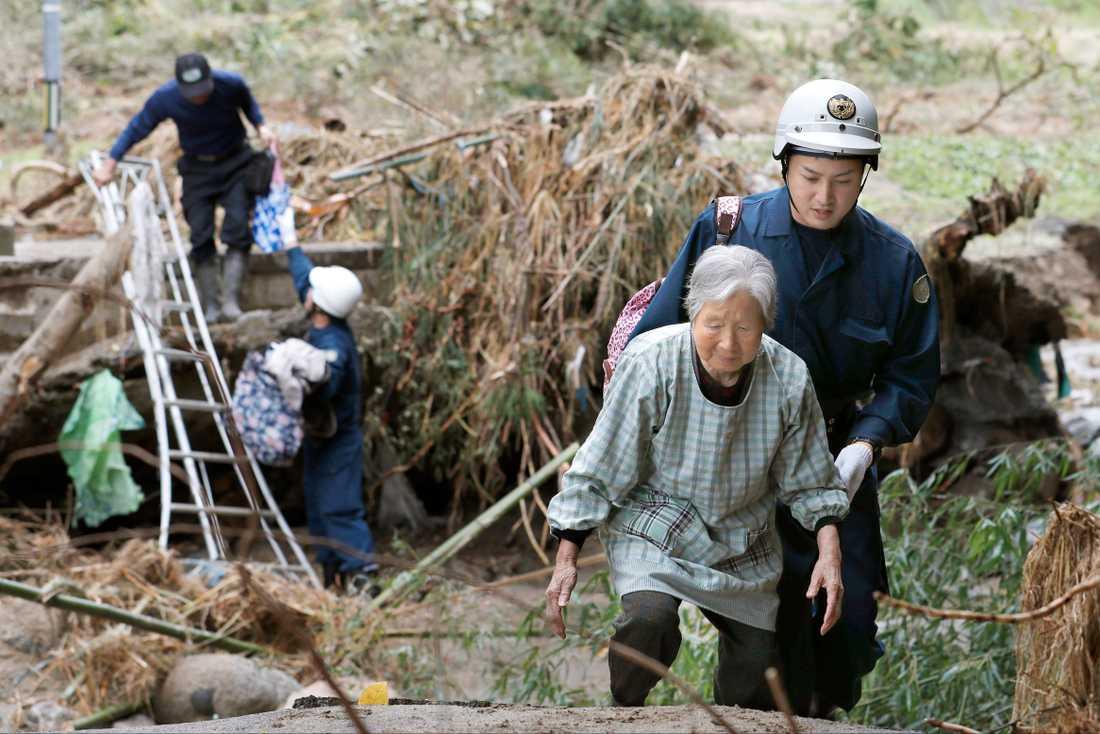 Räddningsarbetare hjälper invånare i Fukushima.