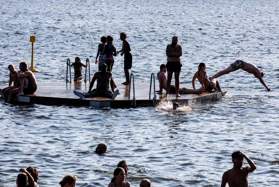 Människor som badar vid Tantolundens badplats i Stockholm i det varma julivädret.