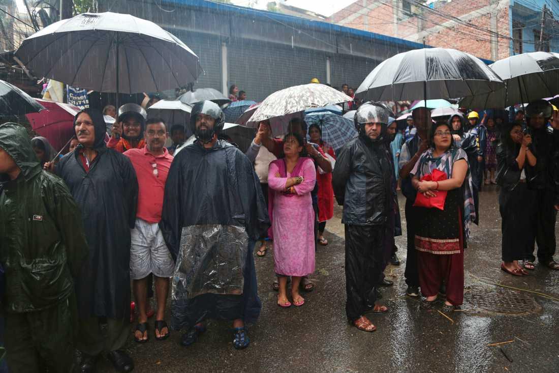 I Katmandu i Nepal tittar människor på när soldater räddar personer från deras översvämmade bostäder.