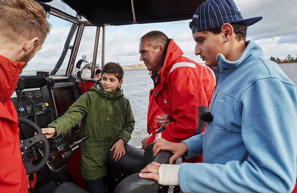 Nils Ingull visar 11-årige Abdulla och hans bror Mahmoud sjöräddningsbåten som ligger i Helgasjön, Växjö. Den är mindre än den båt som de blev upplockade med en kall natt i november 2015. Men det väcker ändå minnen att träffa sjöräddarna och att vara vid havet.