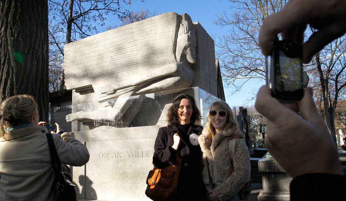 Turister samlas vid Oscar Wildes grav i Paris.