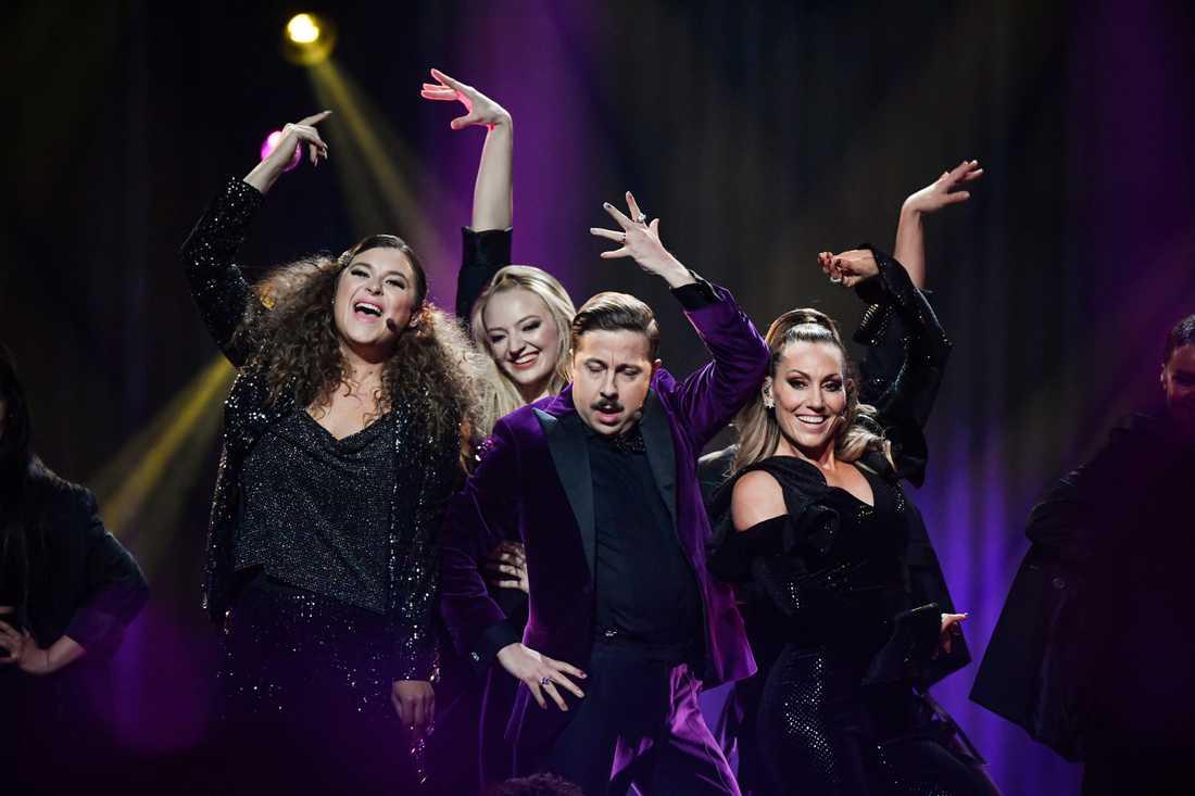 De tre programledarna Lina Hedlund, David Sundin och Linnea Henriksson inledde kvällens deltävling med att framföra en musikalisk hyllning till direktsändningen.