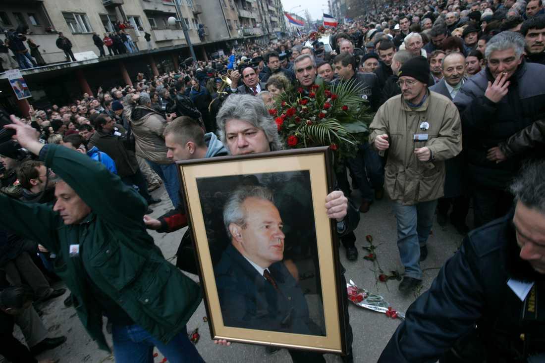 Anhängare till Slobodan Milosevic håller upp bilder föreställande den förre serbiske presidenten under hans begravning i Belgrad, 18 mars 2006.