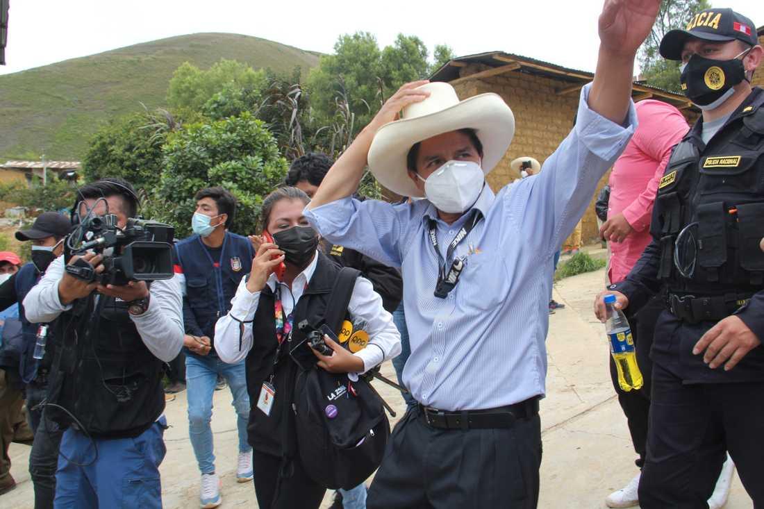 Den peruanske presidentkandidaten Pedro Castillo vinkar till sina anhängare efter att ha röstat i söndagens val.