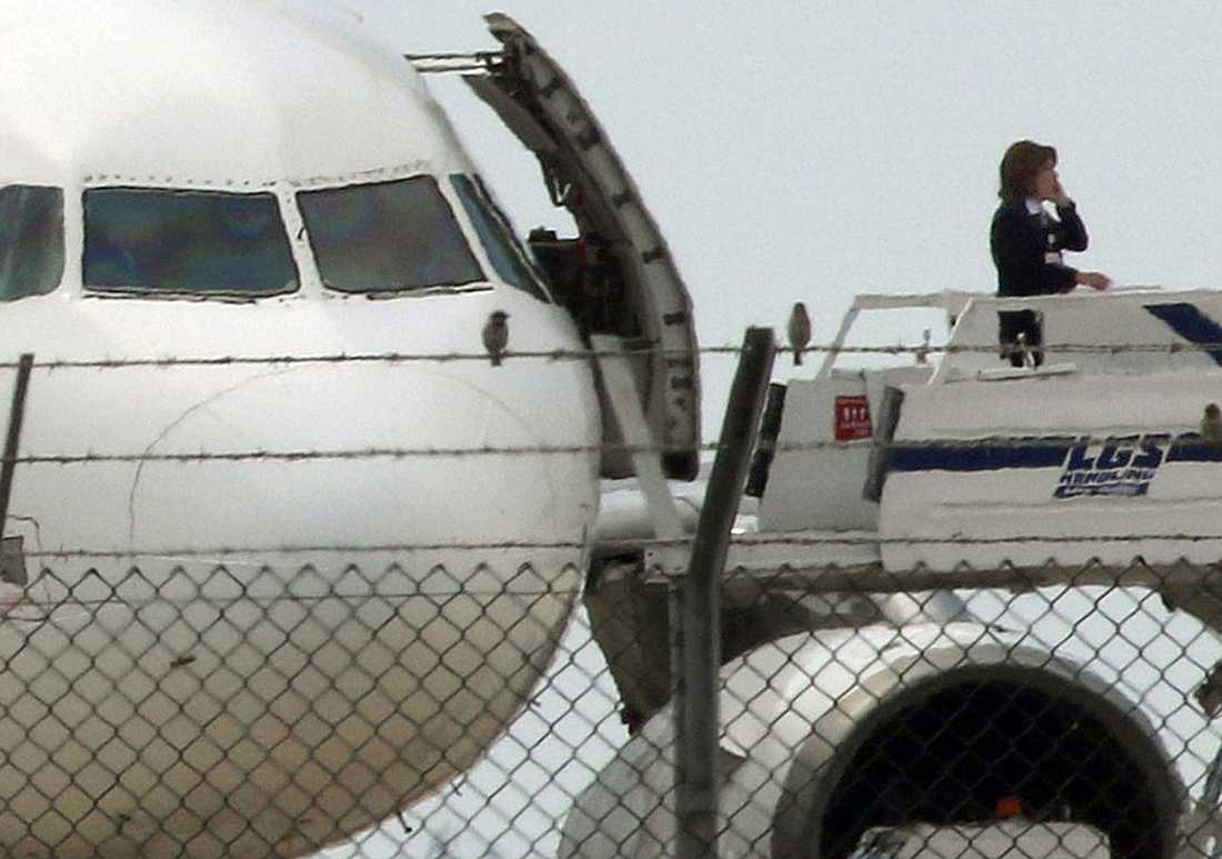 En myndighetsperson ses prata i telefon vid planet, enligt Reuters.