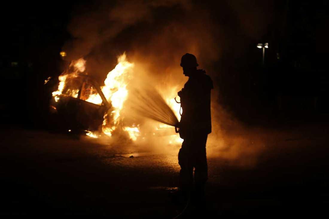 En brandman släcker en bil som brinner i Kista