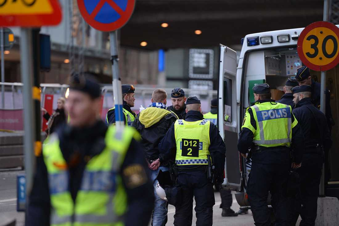 En man med halsduk från polska fotbollslaget Lech Poznan med polis.