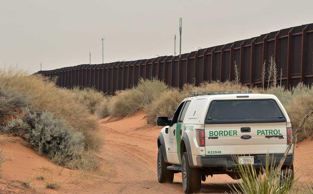 Amerikanska gränsvakter patruller vid befintligt stängsel vid gränsen mot Mexiko