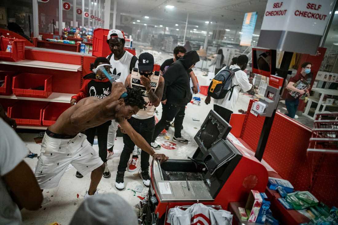 En butiksplundrare använder en hammare för att försöka komma in i en kassaapparat