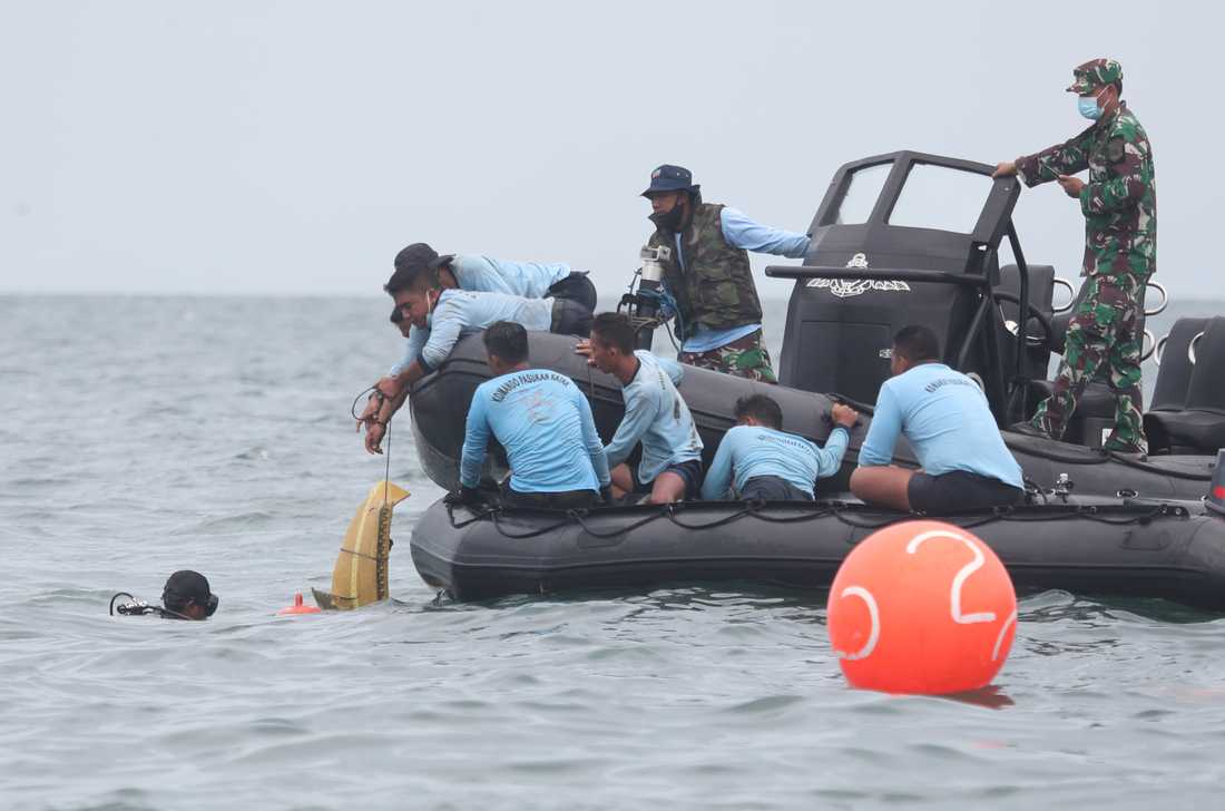Dykare plockar upp delar från det kraschade flygplanet under söndagen.