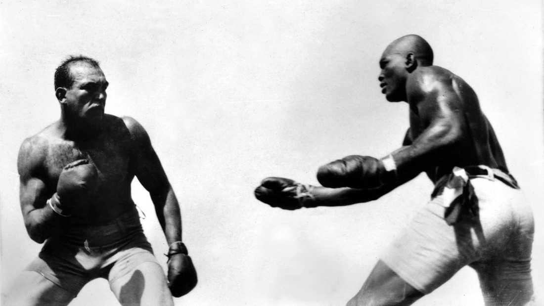 """Jack Johnson (1878-1946) (t.h.) möter Jim """"Stora vita hoppet"""" Jeffries i Nevada 4 juli 1910. Johnson var den förste svarta tungviktsmästaren och hade titeln mellan 1908-1915. Provocerade det vita USA med sin dominans och tvingades i exil under en stor del av sin karriär."""