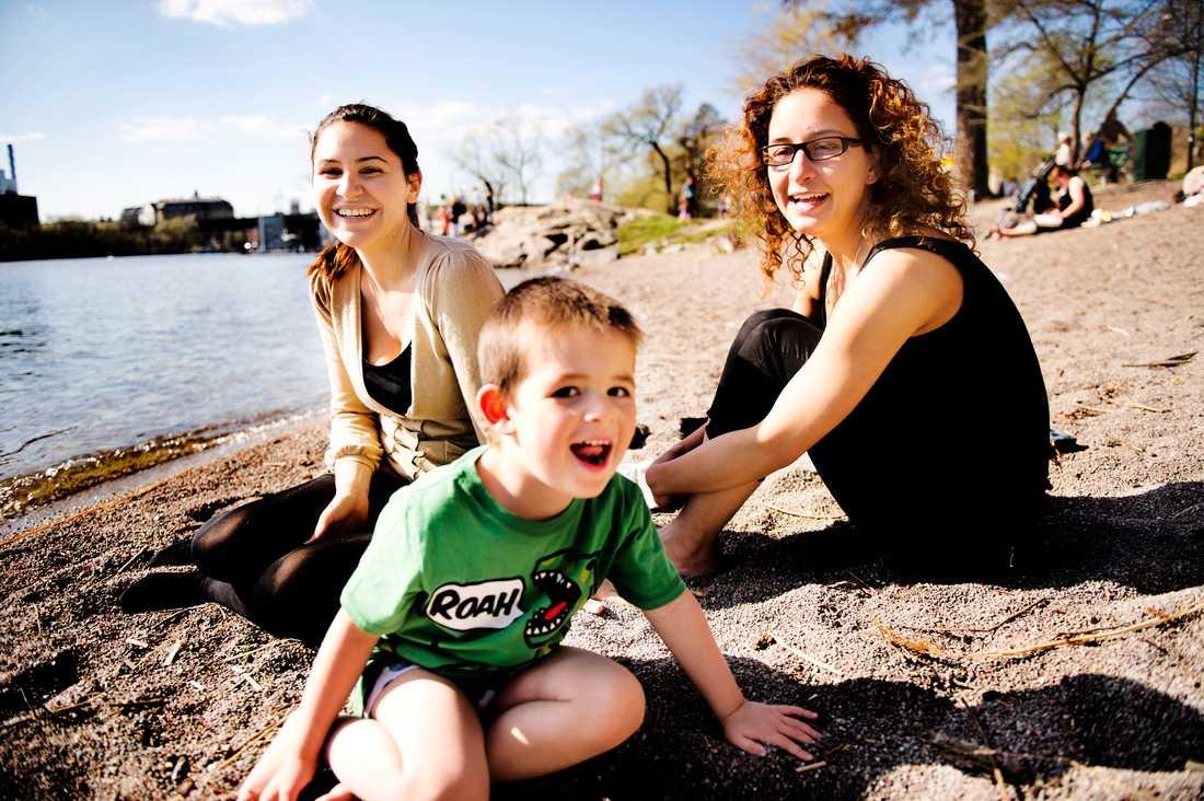 """Derya Erbayraktar, 28, mäklarassistent, sitter på stranden hemma vid Hornstull med väninnan Alev Tahmazidis, 39, student, och hennes son Alexios, 4. """"Jag hade inte förväntat mig att det skulle bli så här varmt. Det är underbart"""", säger Derya. """"Vi har väntat på det här hela vintern! I morgon ska vi grilla"""", säger Alev."""
