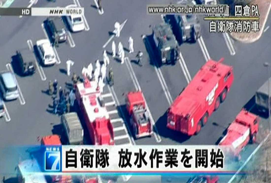 Räddningsarbetare vid Fukushima har sprutade vatten på reaktorerna från brandbilar.
