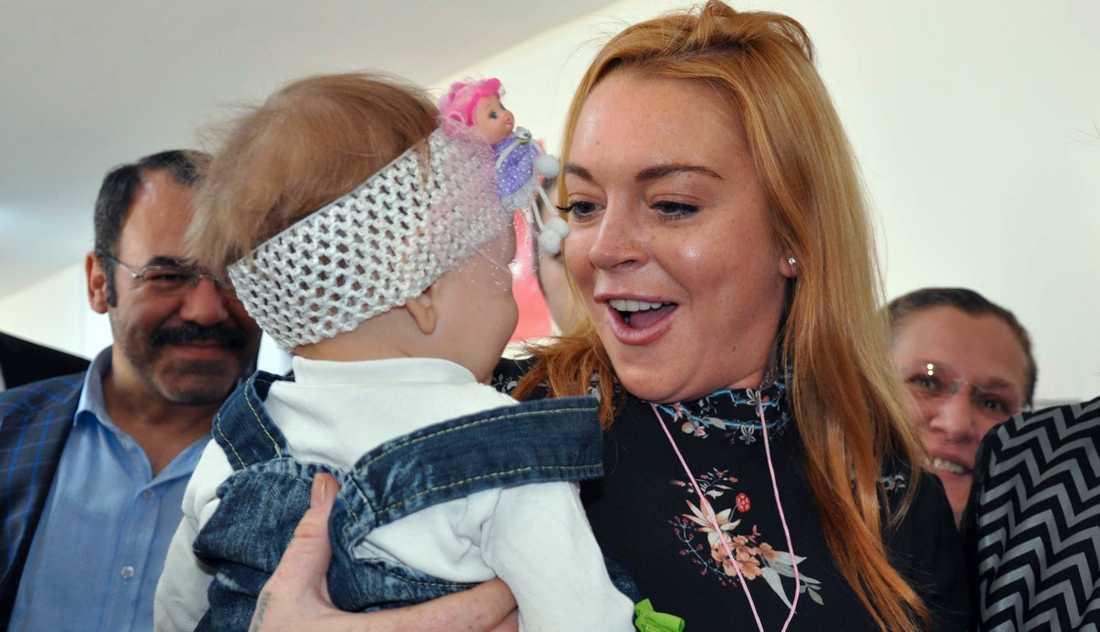 Lindsay Lohan bär ett flyktingbarn från Syrien, under ett besök på en statligt flyktingförläggning i Turkiet.