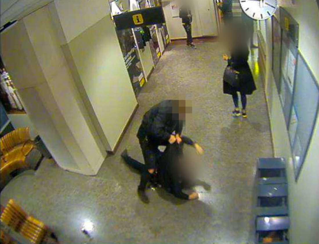 Efter att den misstänkte mannen och polisen båda flugit i golvet ställer sig den misstänkte upp och börjar misshandla polismannen.