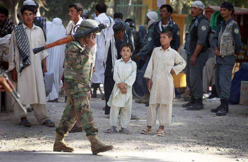 En soldat från ANA, Afghanistan National Army, patrullerar med raketgevär på axeln i centrala Balkh. Barnen tittar på.