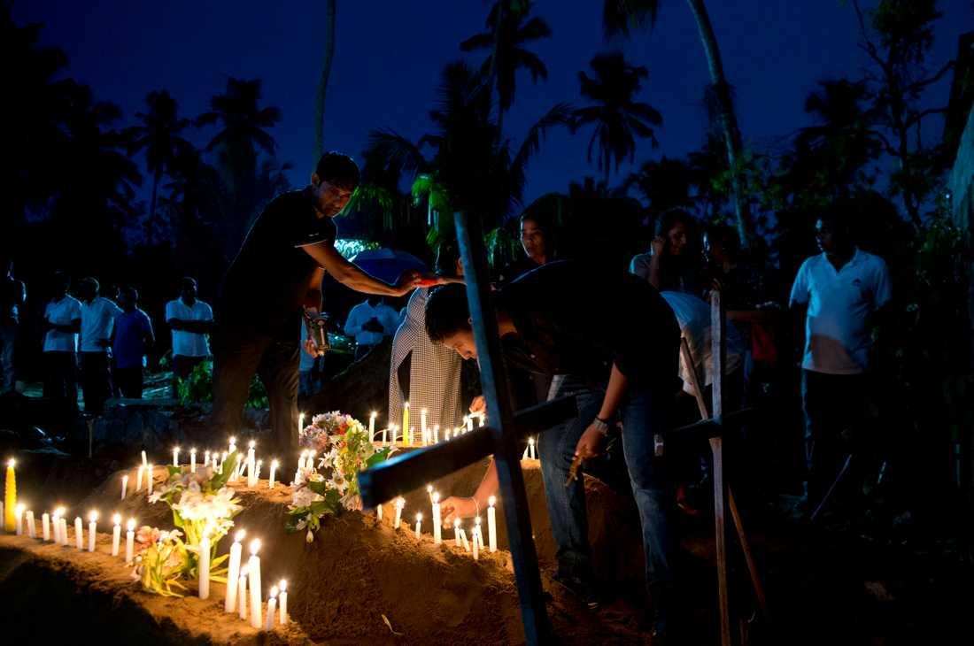 Släktingar tänder ljus för att hedra offren i Sri Lanka.