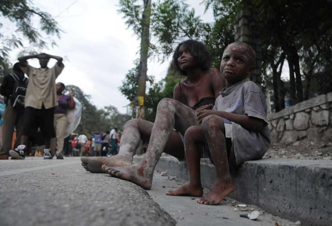 TRAGEDI En skadad pojke och kvinna sitter på en trottoar i centrala Port-au-prince.