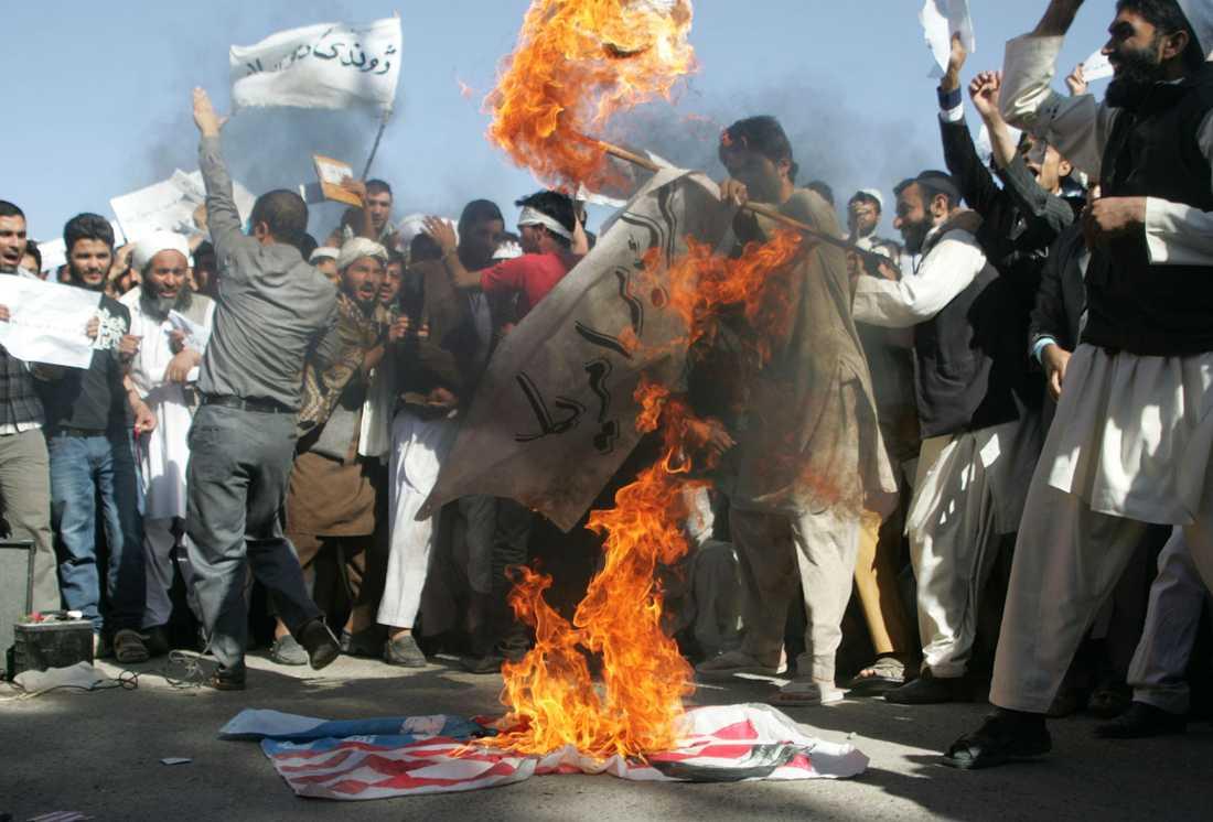 Demonstranter bränner flaggan.