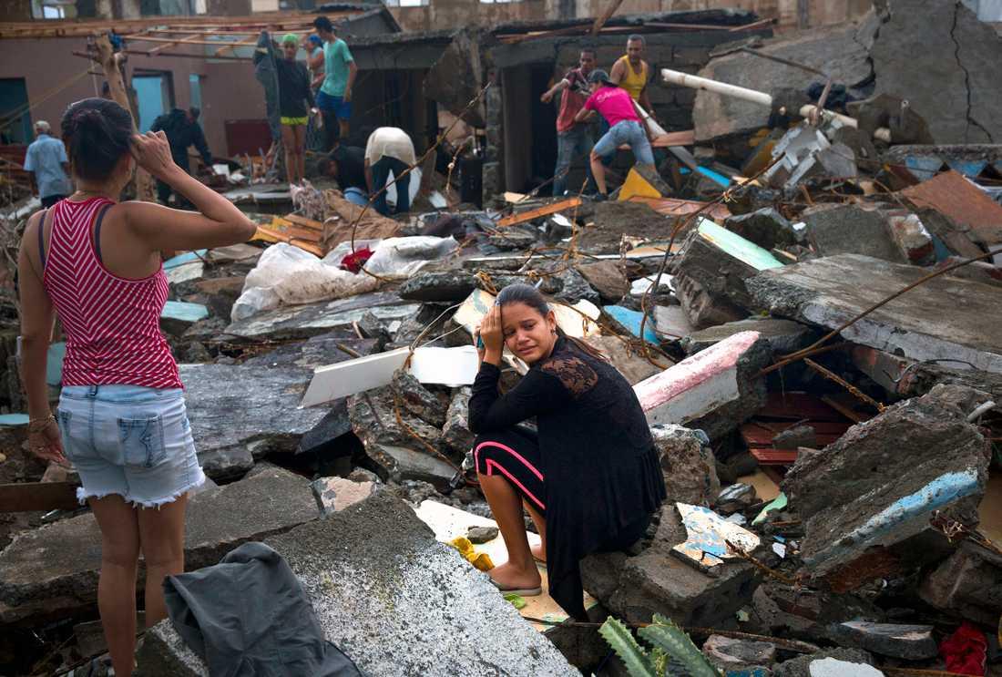 En kvinna på Kuba gråter i resterna efter hennes hem.