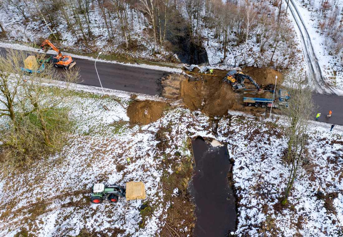 Grävskopor och manskap arbetar med att röja där en vägbro har rasat på Gustavsborgsvägen i Perstorp på torsdagen. Tunnlar under bron har gett vika.